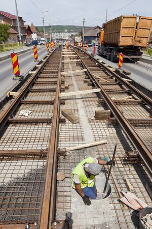 slave labor: railway construction worker in a hole in the street with traffic Stock Photo