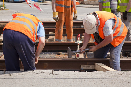 railway worker team in the street with a swinging a hammer