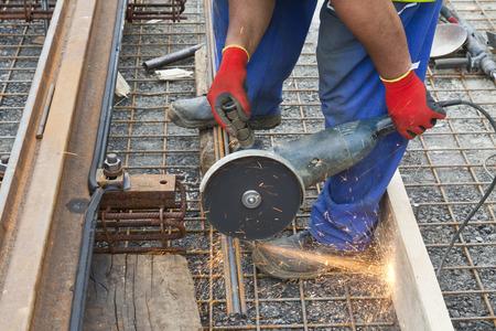man holding grinder cutting metal near a railway