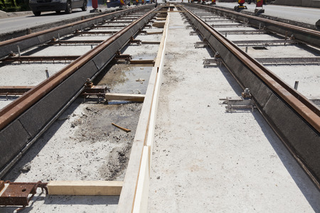 new railway tracks near a busy street in a city with cars on the road Stock Photo