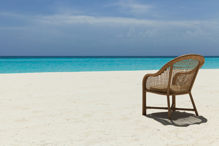 empty chair on a beach with white sand and blue water