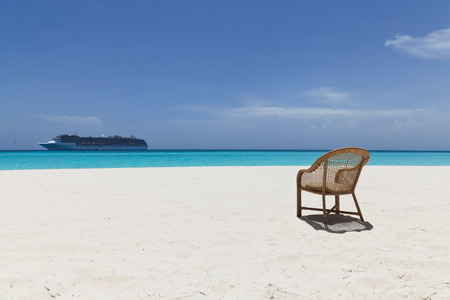 empty chair on beach with cruise ship in the background and clear water Stock Photo