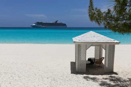 cruise ship close to a beach with a small relaxation building
