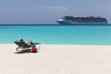 young woman in chair on a beach with cruise ship in the background
