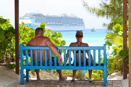 couple siting on a bench in the shade with cruise ship in the background