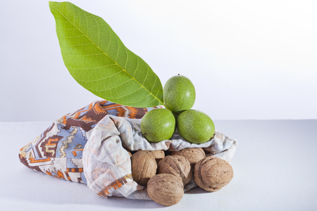 green and ripe walnuts with a leaf from a bag Stock Photo