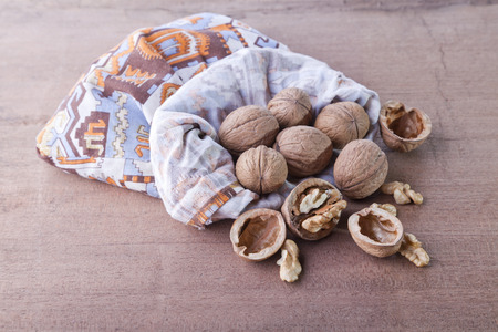 bag of walnuts cracked on a wood background