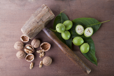 green and ripe walnuts on wood backround with hammer