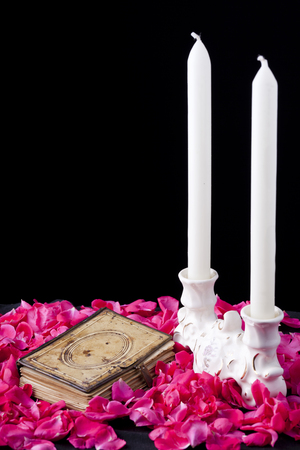 old book on rose petal bed with candles