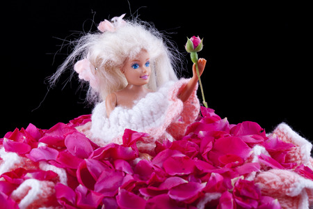 barbie doll full of rose petals holdin a bud in hand
