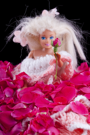 toy dall offering a rose bud from a bed of petals Stock Photo