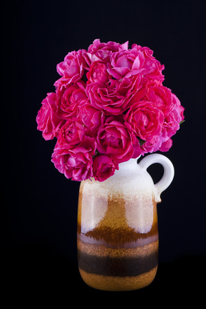 isolated bunch of roses in a vase on black background Stock Photo