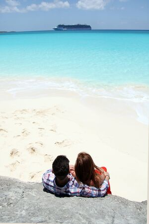 young couple on a secluded beach with cruise ship in the distance in the bahamas