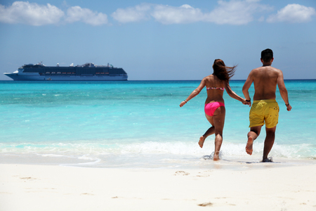 happy couple running in water at the beach with cruise ship close to shore on sunny day Stock Photo
