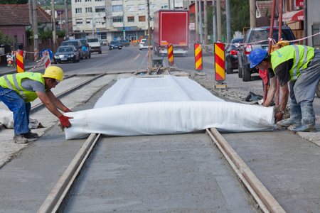 men covering fresh wet cement on the road with cloth Editorial