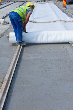 man covering fresh wet cement on the road with cloth