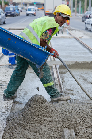 man working with wet concrete on a railway