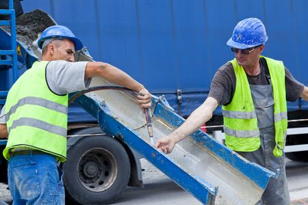 workers washing hands with a hoze from cement