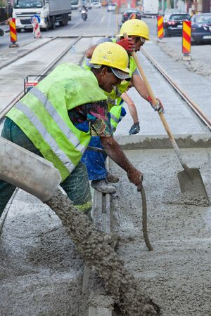 public works: construction team pouring concrete on a road with boots and protection gear Editorial