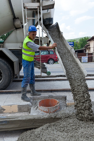 man with cement truck pouring wet material on road Editorial