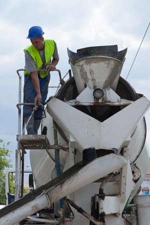 man on a cement machine washing with a hoze
