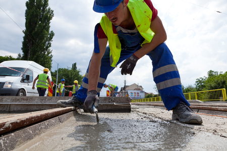 construction team pouring concrete on a road with boots and protection gear Editorial