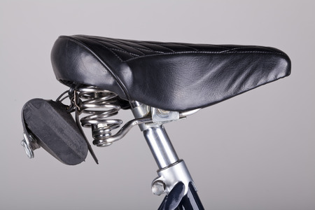 isolated bicycle seat with leather bag on grey