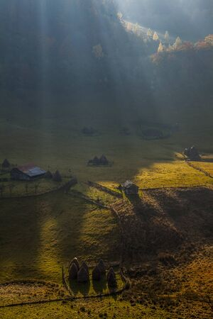morning sun rays on mountain village near forest