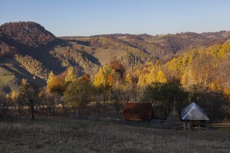 traditional romanian house in colorfull autumn forest with hills