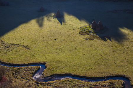 hay stacks with shadow aerial view near river on meadow