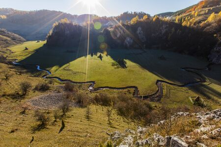 beautiful valley with hay stacks and river at sunrise with green meadow