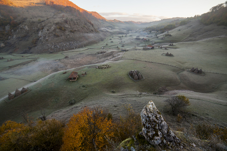 hills and hay stacks in romanian farmlands at sunrise