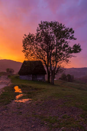 old traditional house in romanian village at sunrise with beautiful colors