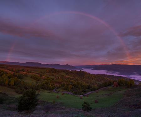 huge rainbow in mountains in autumn with pink sky Stock Photo