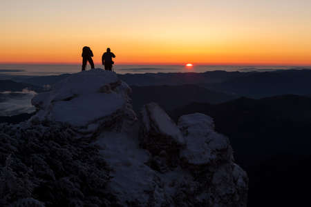 photographer men on snow mountain at red sunrise