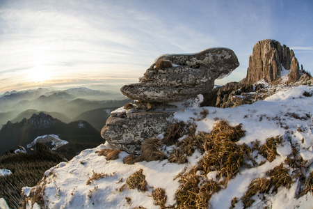 Mountain carpathian romanian landscape in winter with huge boulder at sunset