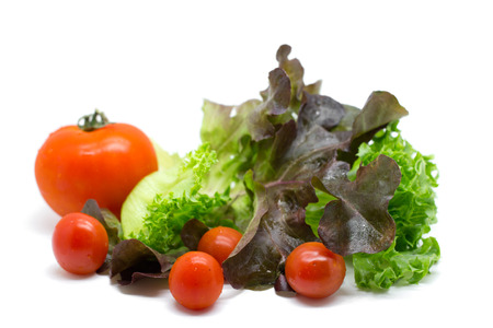 Fresh vegetables and green salad isolated on white  photo
