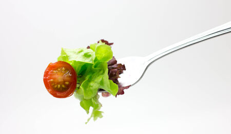 fresh red tomato and salad on a fork. photo
