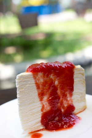 Strawberry crepe cake on white dish. photo