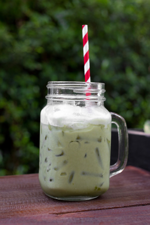a glass of iced green tea latte in the garden photo
