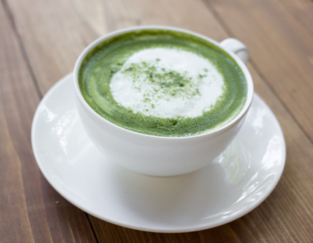 Matcha green tea latte beverage in glass on table. photo
