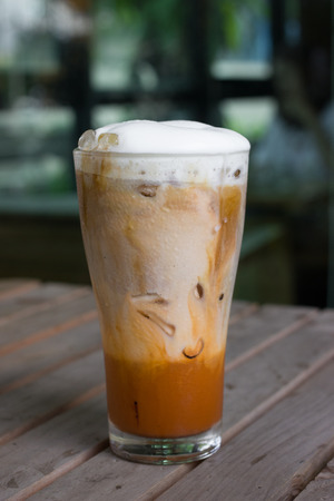 Iced coffee with milk is on the table in cafe. photo