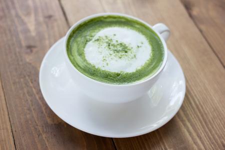 green powder: Matcha green tea latte beverage in glass on table.