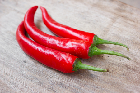 Hot red chili or chilli peppers over wooden background photo