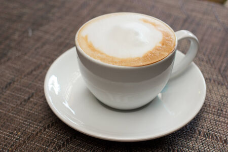 capuchino: cup of coffee with milk on table , in cafe.