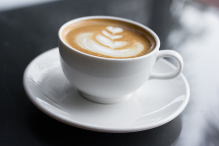 cappuccino cup: Cup of art latte or cappuccino coffee in cafe. Stock Photo
