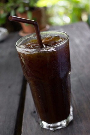 bash: Delicious ice coffee americano on wood table.