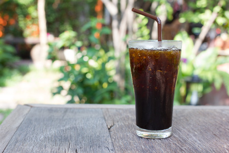 bash: Delicious ice coffee americano on wood table .