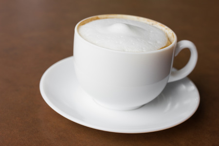 acidity: A cup of cappuccino , in coffee shop.