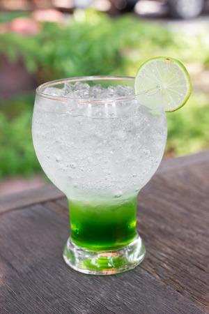 coctel de frutas: copa de cóctel soda.Colorful italiano kiwi en la mesa de madera Foto de archivo